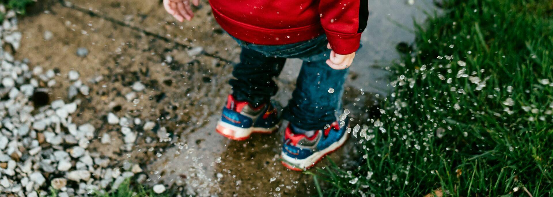 Enfant jouant sous la pluie