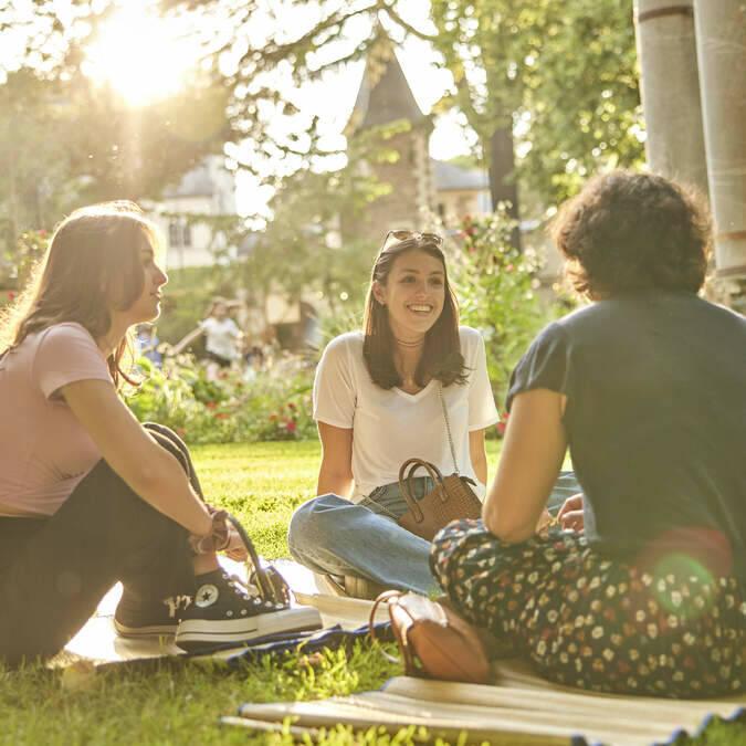 Amis assis dans l'herbe dans un parc